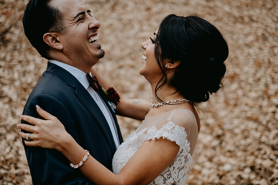 the-guest-ranch-close-up-of-bride-and-groom-laughing-groom-wearing-a-dark-grey-suit-with-light-grey-vest-and-a-burgundy-bowtie-bride-in-a-tulle-ballgown-with-straps-and-a-beaded-bodice