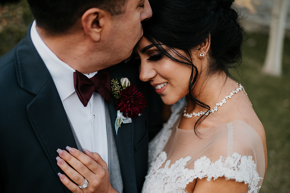 the-guest-ranch-close-up-on-couple-groom-wearing-a-dark-grey-suit-with-light-grey-vest-and-a-burgundy-bowtie-bride-in-a-tulle-ballgown-with-straps-and-a-beaded-bodice