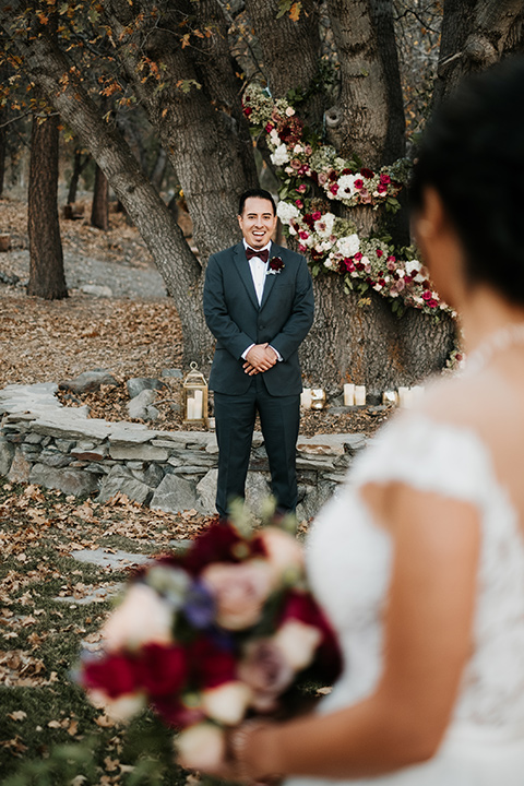 the-guest-ranch-groo-at-ceremony-space-bride-walking-up-groom-in-a-dark-grey-suit-with-light-grey-vest-and-burgundy-bow-bride-in-a-tulle-ball-gown-with-straps-and-a-beaded-bodice