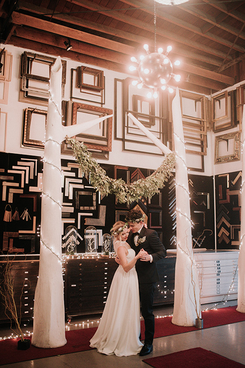 Voila-studios-bride-and-groom-dancing-bride-in-a-flowing-gown-with-a-natural-waistline-and-an-illusion-neckline-with-a-floral-crown-groom-in-a-navy-tuxedo-with-a-leather-bow-tie