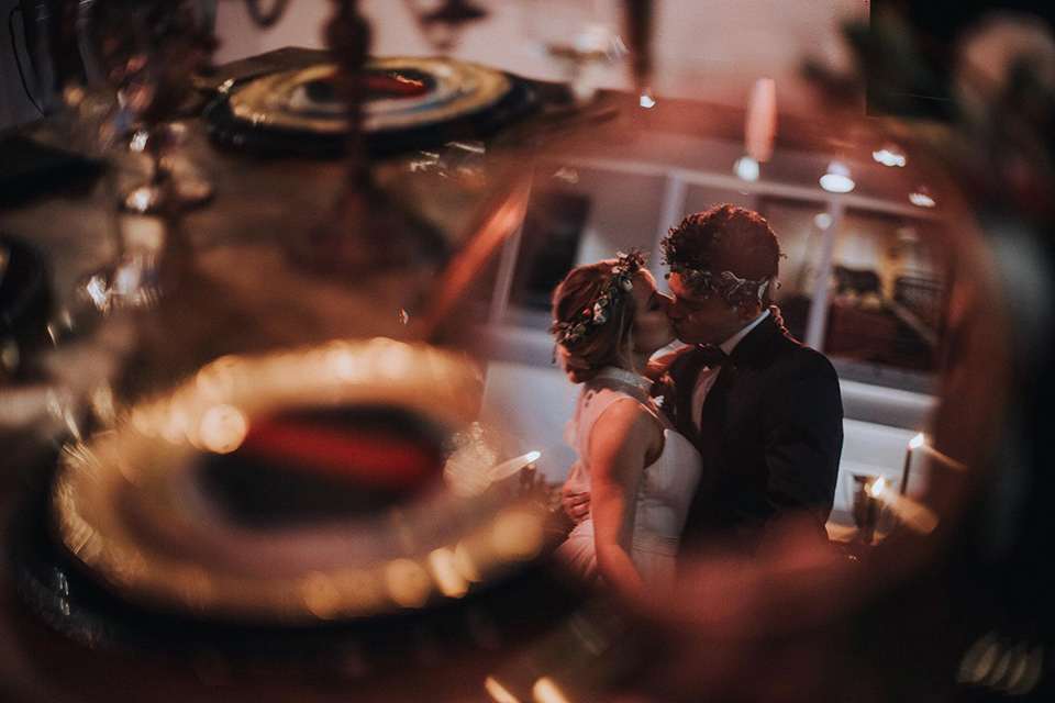Voila-studios-bride-and-groom-kissing-with-table-scape