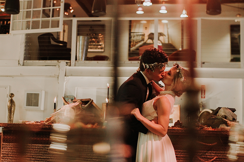Voila-studios-bride-and-groom-kissing-bride-in-a-flowing-gown-with-a-natural-waistline-and-illusion-neckline-and-floral-crown-groom-in-a-navy-tuxedo-with-leather-bow-tie