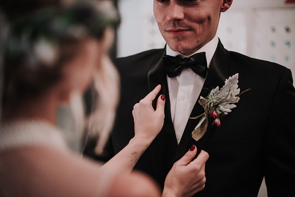 Voila-studios-bride-touching-jacket-bride-in-a-flowing-gown-with-a-natural-waistline-and-illusion-neckline-and-floral-crown-groom-in-a-navy-tuxedo-with-leather-bow-tie