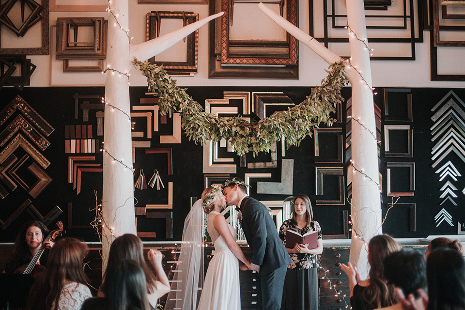 Voila-studios-ceremony-kiss-bride-in-a-flowing-gown-with-a-natural-waistline-and-illusion-neckline-and-floral-crown-groom-in-a-navy-tuxedo-with-leather-bow-tie