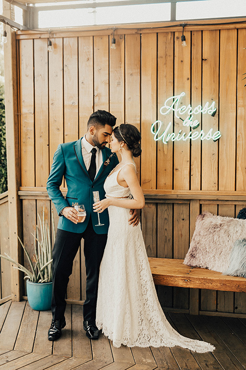 The-Ruby-Street-photoshoot-bride-and-groom-by-wooden-wall-groom-in-a-teal-tuxedo-jacket-with-black-pants-and-a-black-bowtie-bride-in-a-lace-dress-with-a-deep-v-neckline