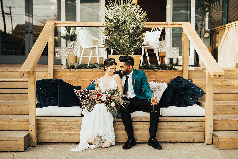 The-Ruby-Street-photoshoot-bride-and-groom-sitting-outside-groom-in-a-teal-tuxedo-with-black-pants-and-bride-in-a-lace-bohemian-dress