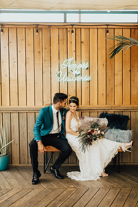 The-Ruby-Street-photoshoot-bride-and-groom-sitting-under-neon-lights-groom-wearing-a-teal-jacket-with-black-pants-bride-wearing-a-lace-bohemian-style-dress