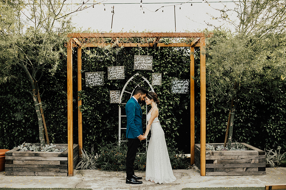 The-Ruby-Street-photoshoot-bride-and-groom-under-ceremony-arch-groom-in-a-teal-tuxedo-with-black-pants-and-bride-in-a-lace-bohemian-dress