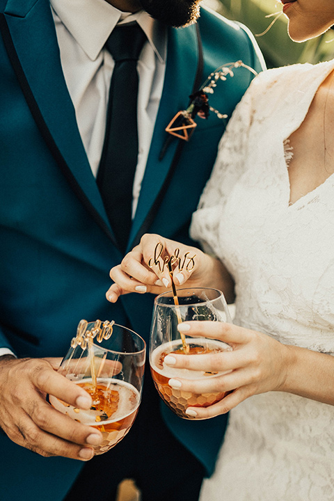 The-Ruby-Street-photoshoot-close-up-on-drinks-groom-wearing-a-teal-blue-tuxedo-and-the-bride-wearing-a-lace-dress