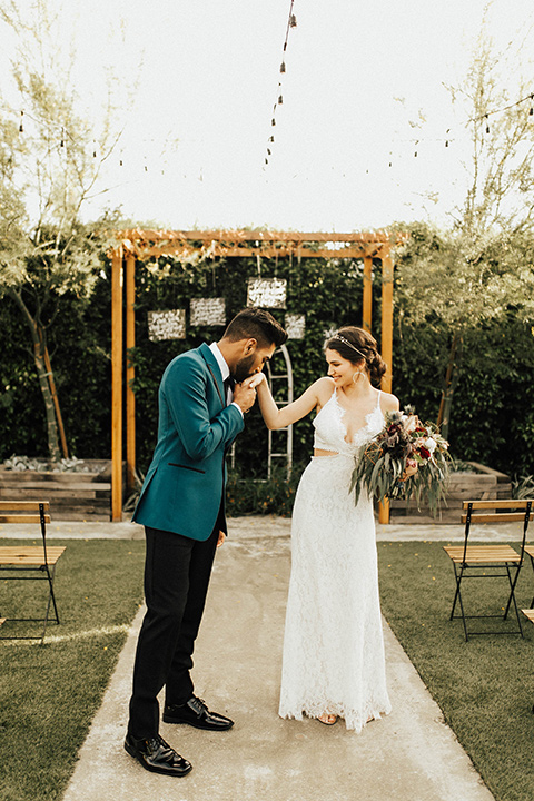 The-Ruby-Street-photoshoot-groom-kissing-brides-hand-groom-wearing-a-teal-jacket-with-black-pants-bride-wearing-a-lace-bohemian-style-dress