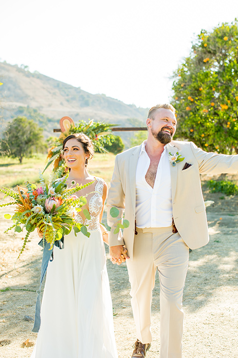 A-Stones-Throw-Winery-African-Shoot-bride-and-groom-after-ceremony-bride-wearing-an-a-line-gown-with-a-plunging-neckline-and-straps-groom-in-a-tan-suit-with-brown-suspenders