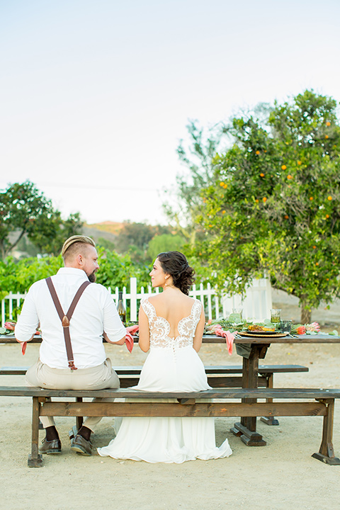 A-Stones-Throw-Winery-African-Shoot-bride-and-groom-at-picnic-table-bride-in-an-a-line-white-gown-with-lace-detailed-straps-and-groom-in-a-tan-suit-with-brown-suspenders