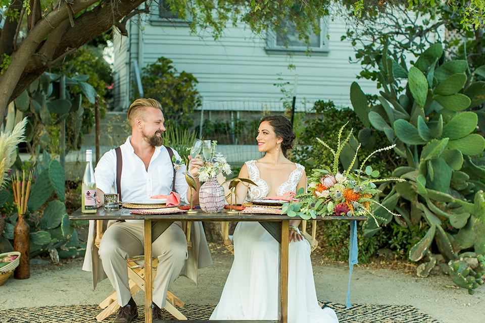 A-Stones-Throw-Winery-African-Shoot-bride-and-groom-at-sweetheart-tables-bride-in-an-a-line-gown-with-lace-straps-groom-in-a-tan-suit-with-brown-accessories-and-susenders