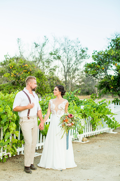 A-Stones-Throw-Winery-African-Shoot-bride-and-groom-by-fence-groom-holding-suspenders-bride-wearing-an-a-line-gown-with-a-plunging-neckline-and-straps-groom-in-a-tan-suit-with-brown-suspenders