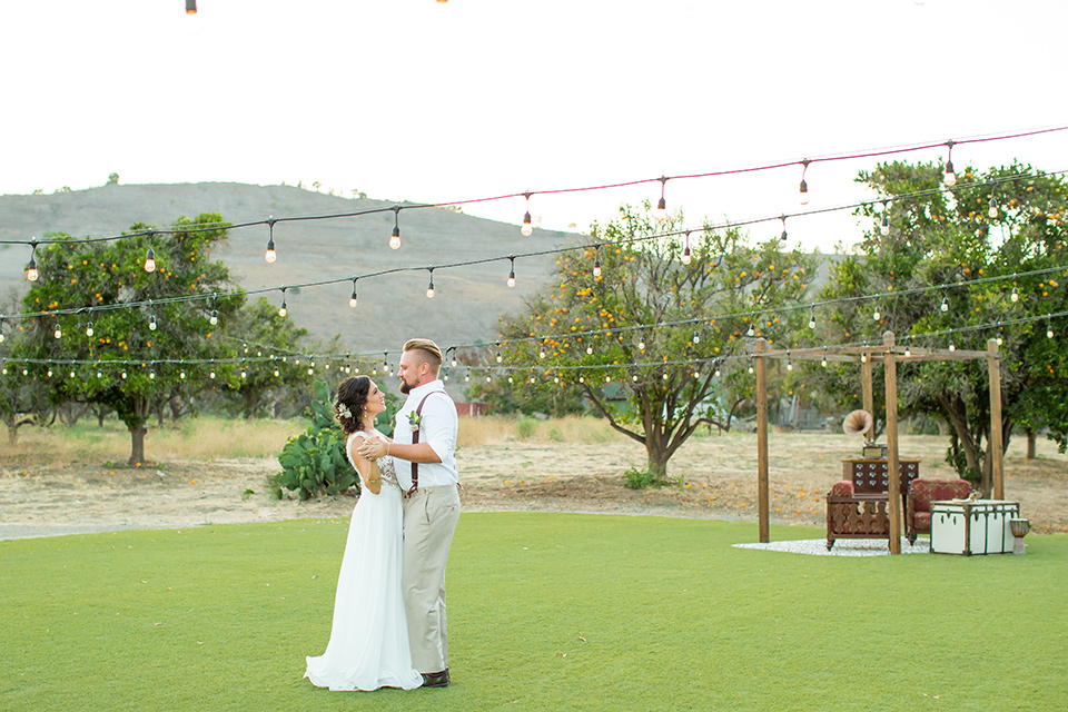 A-Stones-Throw-Winery-African-Shoot-bride-and-groom-dancing-under-string-lights-bride-in-an-a-line-gown-with-lace-straps-groom-in-a-tan-suit-with-brown-accessories-and-susenders