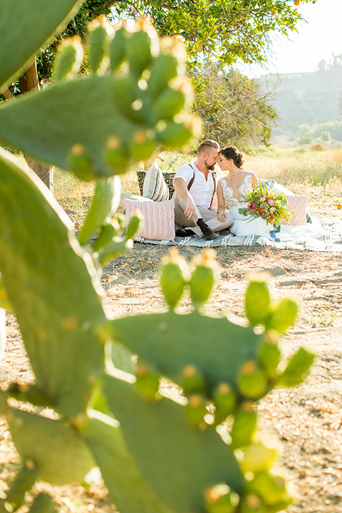 A-Stones-Throw-Winery-African-Shoot-bride-and-groom-on-picnic-blanket-bride-in-an-a-line-white-gown-with-lace-detailed-straps-and-groom-in-a-tan-suit-with-brown-suspenders