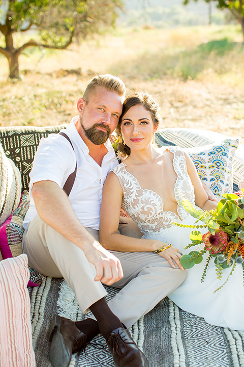 A-Stones-Throw-Winery-African-Shoot-bride-and-groom-sitting-on-blanket-bride-wearing-an-a-line-gown-with-a-plunging-neckline-and-straps-groom-in-a-tan-suit-with-brown-suspenders