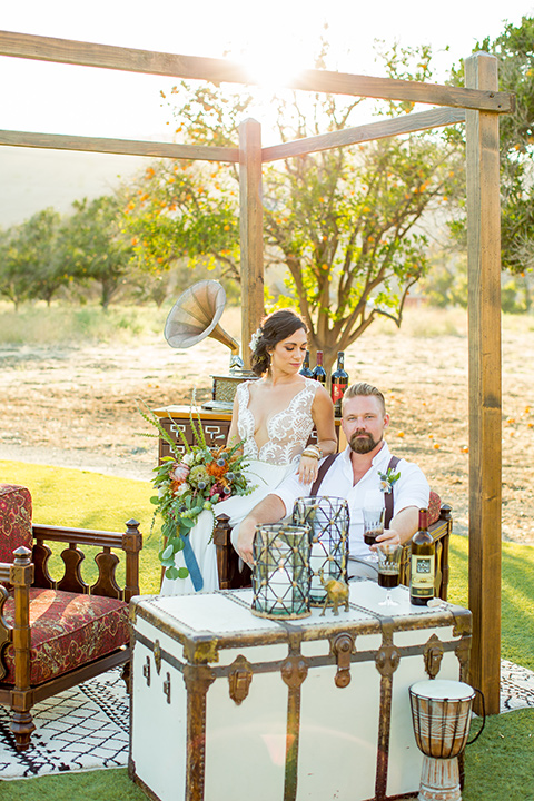 A-Stones-Throw-Winery-African-Shoot-bride-and-groom-sitting-under-canopy-bride-in-an-a-line-white-gown-with-lace-detailed-straps-and-groom-in-a-tan-suit-with-brown-suspenders