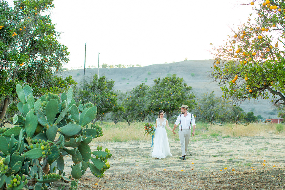 A-Stones-Throw-Winery-African-Shoot-bride-and-groom-walking-in-grass-field-bride-in-an-a-line-gown-with-lace-straps-groom-in-a-tan-suit-with-brown-accessories-and-susenders