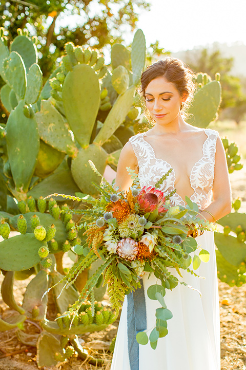 A-Stones-Throw-Winery-African-Shoot-bride-looking-at-florals-bride-wearing-an-a-line-gown-with-a-plunging-neckline-and-straps