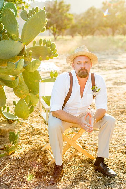 A-Stones-Throw-Winery-African-Shoot-groom-in-hat-looking-at-camera-in-a-tan-suit-with-brown-suspenders