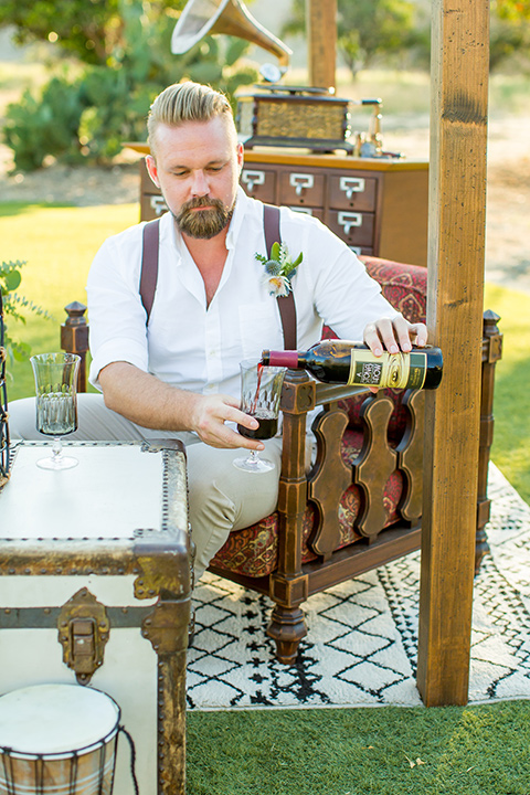 A-Stones-Throw-Winery-African-Shoot-groom-pouring-wine-in-a-tan-suit-with-brown-suspenders
