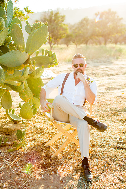 A-Stones-Throw-Winery-African-Shoot-groom-sitting-in-chair-with-glasses-in-a-tan-suit-with-brown-suspenders