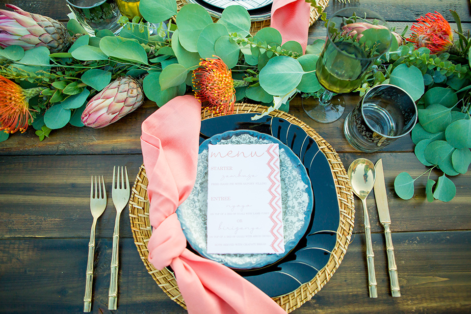 A-Stones-Throw-Winery-African-Shoot-table-flatware-with-gold-and-blue-plates-and-gold-flateware-and-pink-napkins