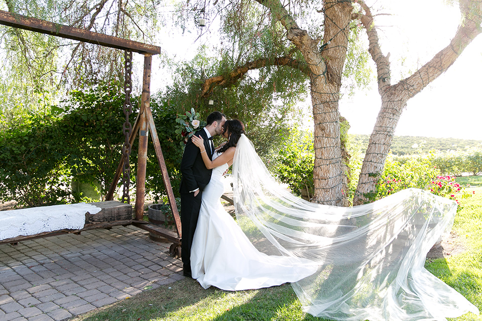 Villa-de-Amore-bride-and-groom-kissing-with-her-veil-blowing-in-the-wind