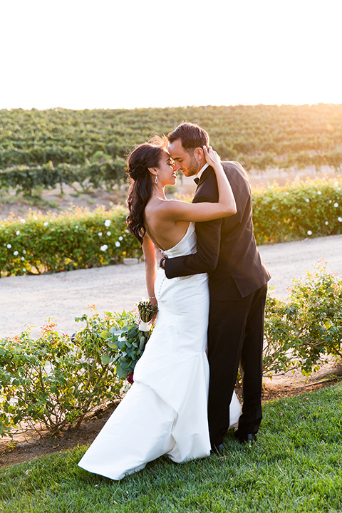 Villa-de-Amore-bride-and-groom-kissing-with-sun-setting-bride-and-groom-by-ivy-bride-in-a-fitted-gown-groom-in-a-black-tuxedo