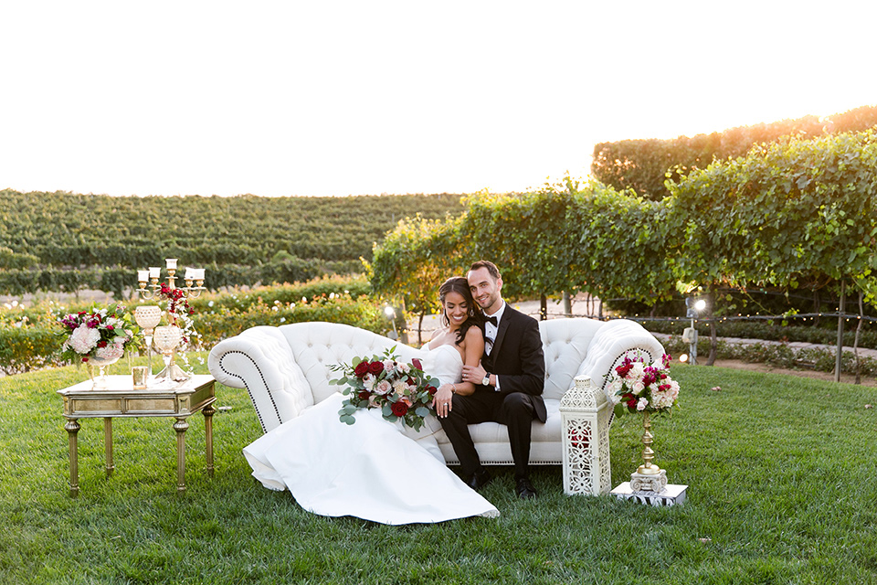 Villa-de-Amore-bride-and-groom-on-couch-bride-in-a-fitted-gown-groom-in-a-black-tuxedo