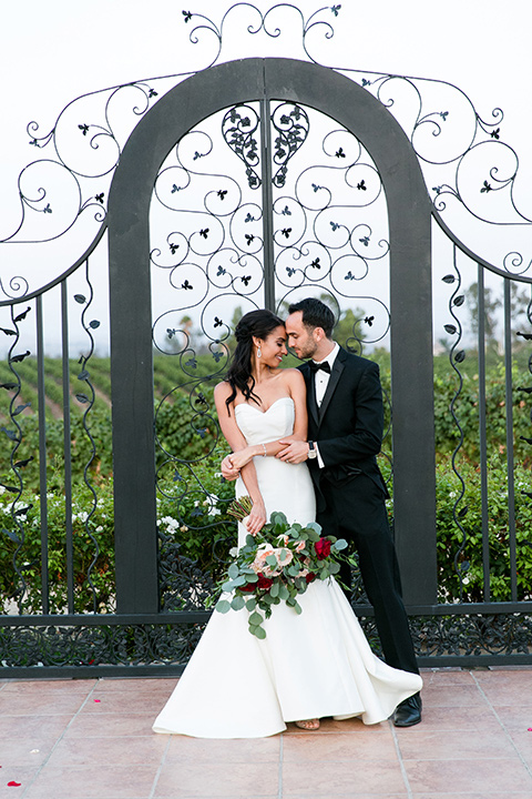 Villa-de-Amore-couple-touching-heads-by-iron-gate-bride-in-a-fitted-gown-groom-in-a-black-tuxedo
