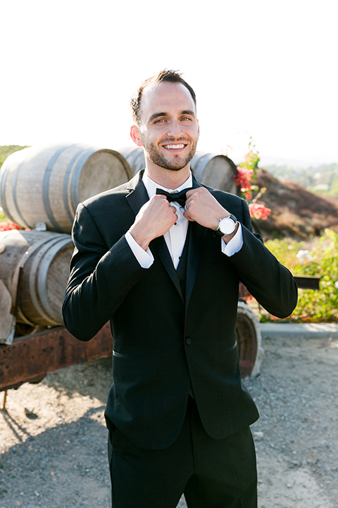 Villa-de-Amore-groo-looking-at-camera-touching-bow-tie-groom-in-a-black-tuxedo