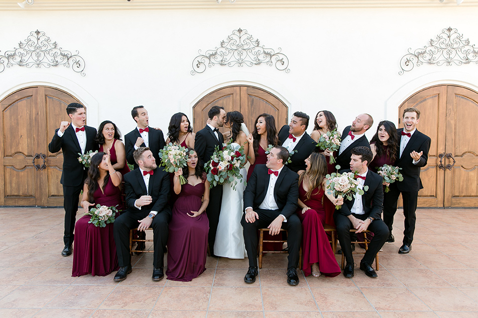 villa-de-Amore-bridalparty-bride-in-a-strapless-gown-with-bridesmaids-in-alternating-red-dresses-groom-and-groomsmen-in-black-tuxedos