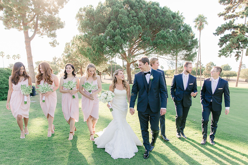 Los-Verdes-Golf-Course-Wedding-bridalparty-walking-bridesmaids-in-light-pink-short-dresses-groomsmen-in-blue-suits-with-light-pink-bowties-bride-is-in-a-lace-mermaid-style-gown-with-a-modified-sweetheart-neckline-the-groom-is-in-a-navy-blue-tuxedo-with-a-black-shawl-lapel-and-a-black-bow-tie