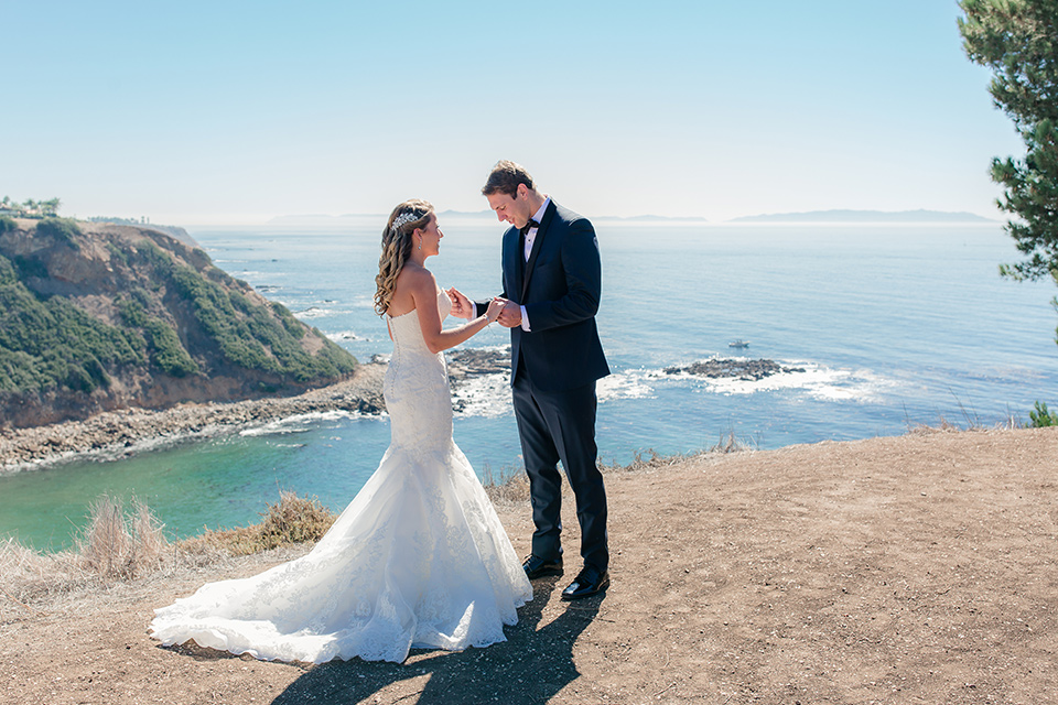 Los-Verdes-Golf-Course-Wedding-bride-and-groom-first-look-bride-is-in-a-lace-mermaid-style-gown-with-a-modified-sweetheart-neckline-the-groom-is-in-a-navy-blue-tuxedo-with-a-black-shawl-lapel-and-a-black-bow-tie