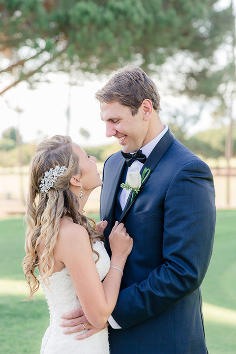 Los-Verdes-Golf-Course-Wedding-bride-and-groom-looking-at-each-other-bride-in-white-lace-mermaid-gown-and-the-groom-is-in-a-navy-blue-shawl-lapel-tuxedo-and-black-bow-tie