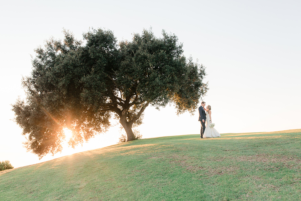 Los-Verdes-Golf-Course-Wedding-bride-and-groom-near-giant-tree-bride-is-in-a-lace-mermaid-style-gown-with-a-modified-sweetheart-neckline-the-groom-is-in-a-navy-blue-tuxedo-with-a-black-shawl-lapel-and-a-black-bow-tie