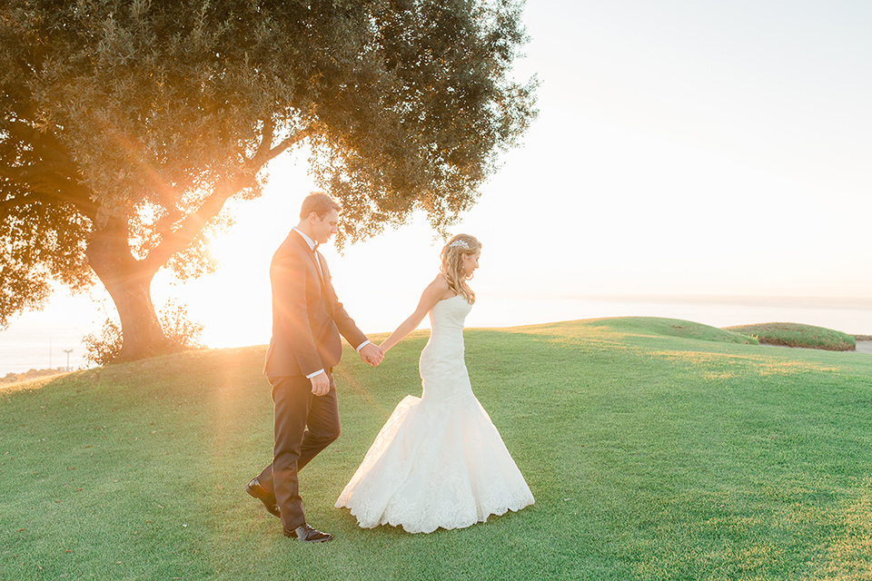 Los-Verdes-Golf-Course-Wedding-bride-and-groom-walking-by-tree-bride-is-in-a-lace-mermaid-style-gown-with-a-modified-sweetheart-neckline-the-groom-is-in-a-navy-blue-tuxedo-with-a-black-shawl-lapel-and-a-black-bow-tie