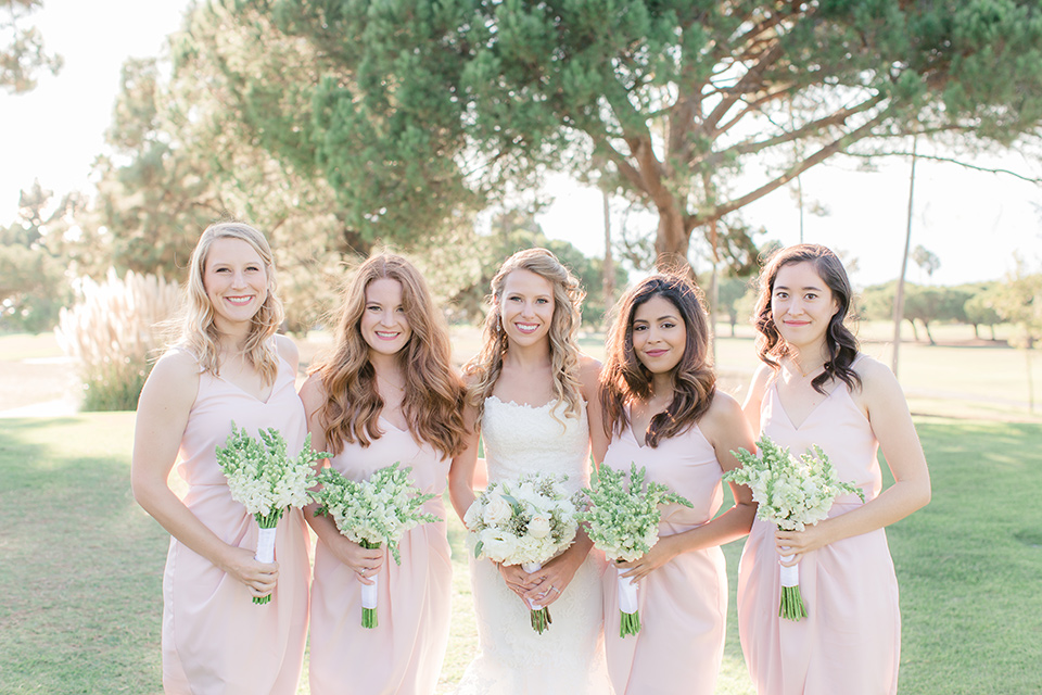 Los-Verdes-Golf-Course-Wedding-bridesmaids-bridesmaids-in-light-pink-short-dresses-bride-is-in-a-lace-mermaid-style-gown-with-a-modified