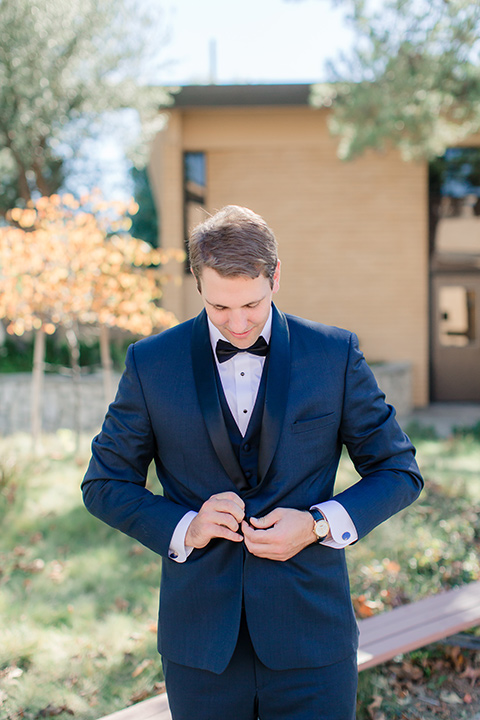 Los-Verdes-Golf-Course-Wedding-groom-buttoning-jacket-in-a-navy-blue-shawl-lapel-tuxedo-and-black-bow-tie