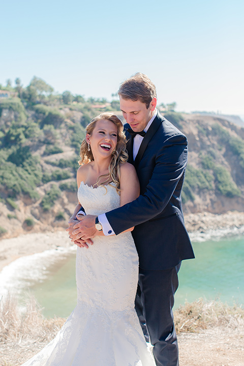 Los-Verdes-Golf-Course-Wedding-groom-holding-bride-from-behind-bride-is-in-a-lace-mermaid-gown-with-a-modified-sweetheart-neckline-and-the-groom-is-in-a-navy-blue-shawl-lapel-tuxedo