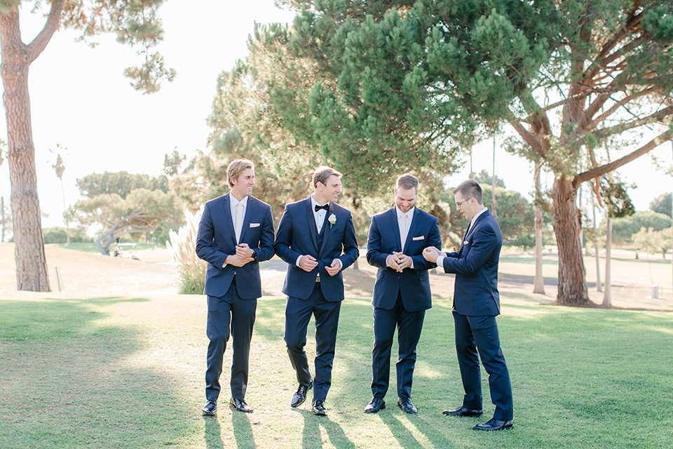 Los-Verdes-Golf-Course-Wedding-groomsman-walking-groomsmen-in-navy-blue-suits-the-groom-is-in-a-navy-blue-tuxedo-with-a-black-shawl-lapel-and-a-black-bow-tie