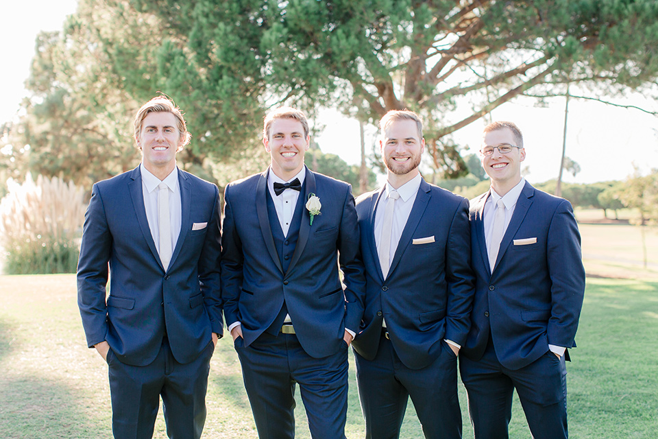 Los-Verdes-Golf-Course-Wedding-groomsmen-in-navy-blue-suits-the-groom-is-in-a-navy-blue-tuxedo-with-a-black-shawl-lapel-and-a-black-bow-tie