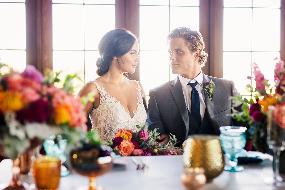 Aliso Viejo wedding design with the bride in a lace gown with thin straps and the groom in a grey suit with a blue neck tie