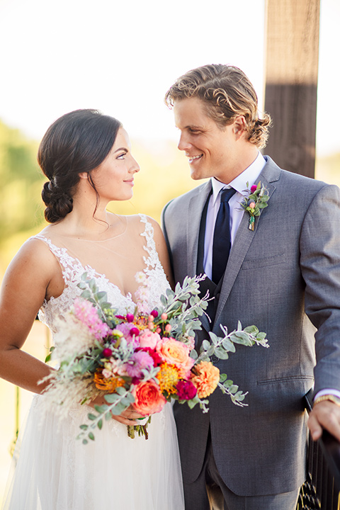 aliso viejo wedding design with the bride in a lace white gown with thin straps and a full skirt and the groom in a grey suit and navy neckline