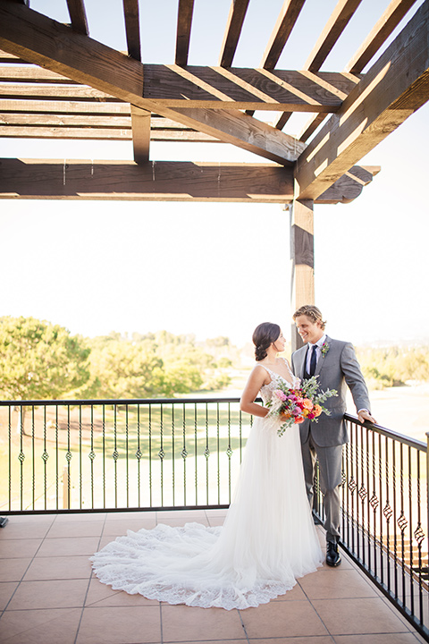 aliso Viejo wedding design with the bride and groom on the patio the bride is in a lace gown with thin straps and the groom in a grey suit with a navy neck tie