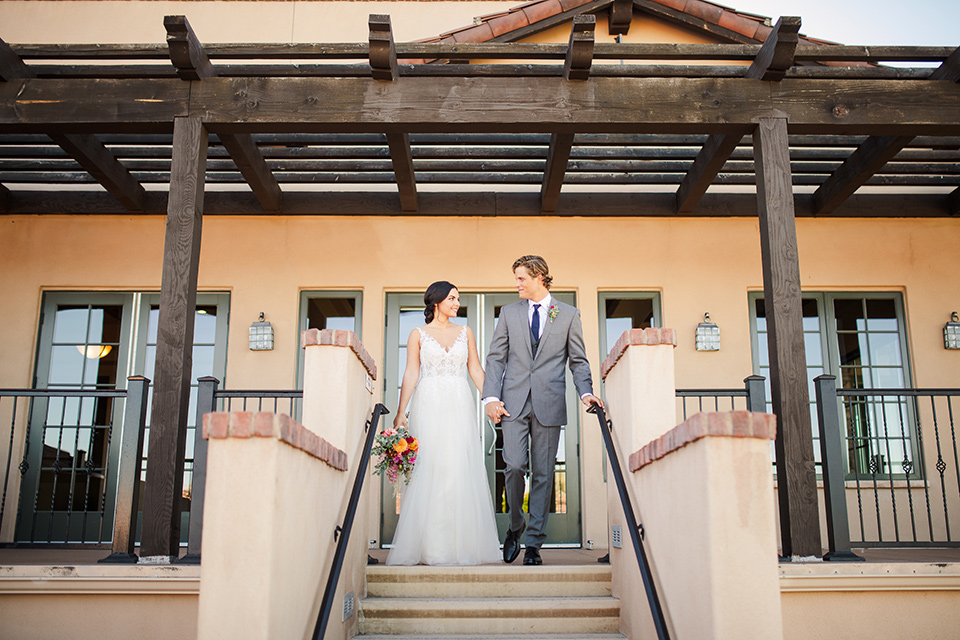 Aliso Viejo wedding design with the bride  and groom at the top of the stairs the bride in a lace gown with thin straps and the groom in a grey suit with a blue neck tie