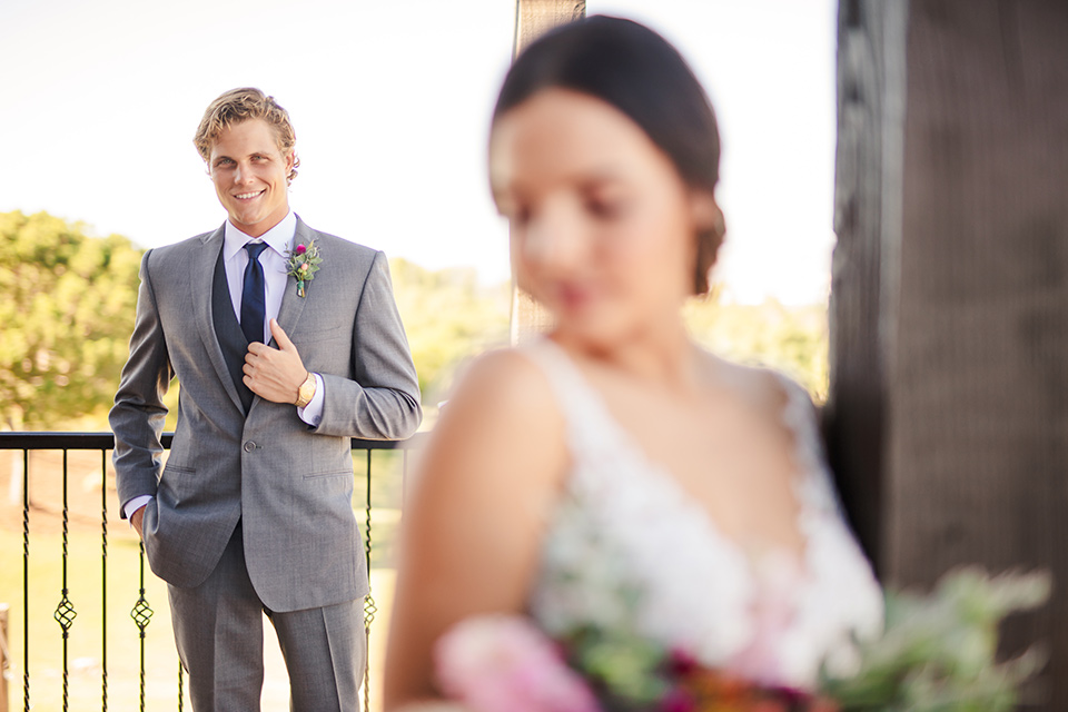 Aliso Viejo wedding design with the bride  and groom outside the bride in a lace gown with thin straps and the groom in a grey suit with a blue neck tie