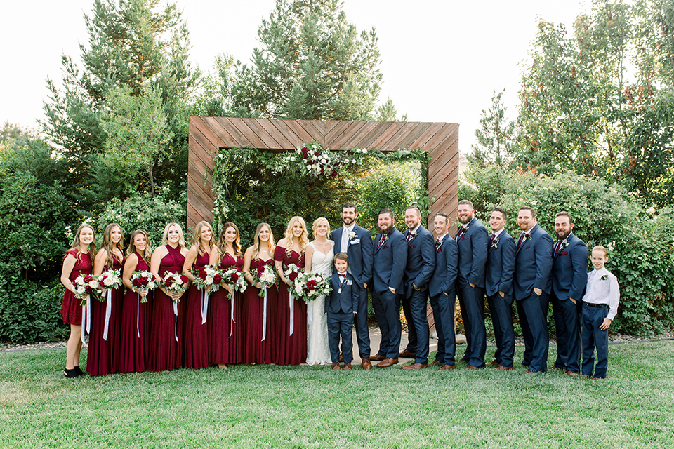 Burgundy-and-Blue-wedding-bridalparty-brdesmaids-in-burgundy-gowns-groomsmen-in-dark-blue-suits-bride-in-a-formfitting-white-lace-gown-with-a-strapless-neckline-the-groom-is-in-a-dark-blue-suit-with-an-ivory-long-tie